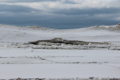 A break in the ice at the distant edge shows the thickness, about 1 foot. Notice the sand mixed in with the ice.