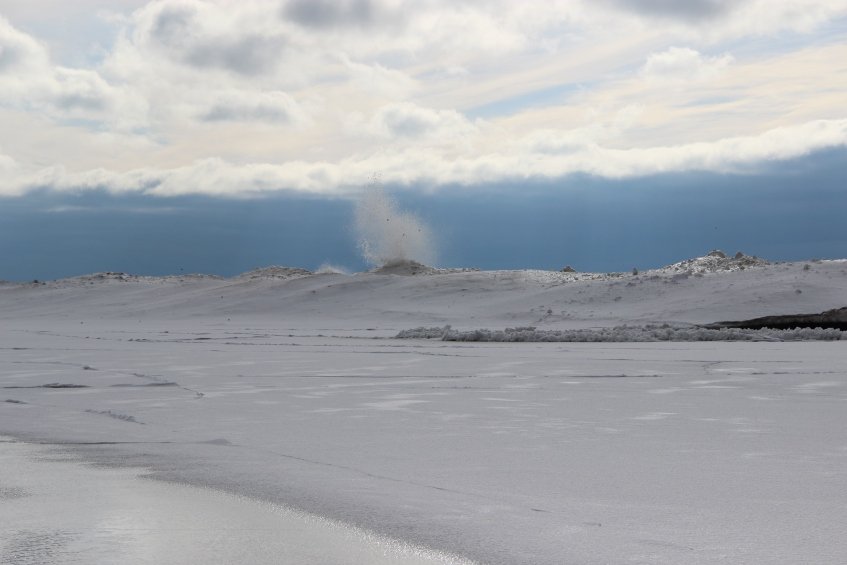 Wave-formed sand dunes line the edge of the floe;  waves crashing up onto the ice floe from open water behind it.